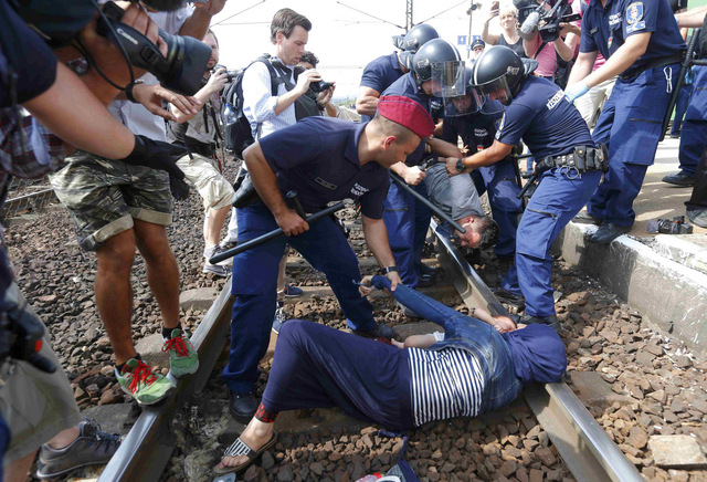 Migrants cling to Hungarian train while lawmakers debate sealing border