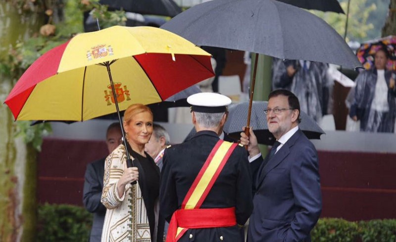 Madrid president sports patriotic umbrella at rainy Armed Forces Day parade