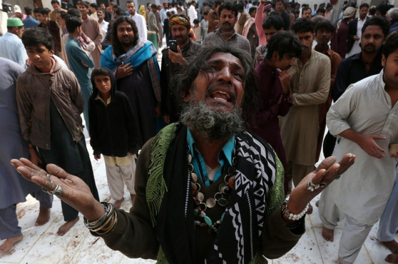 Wailing and anger at Sufi shrine in Pakistan after bomber kills 77